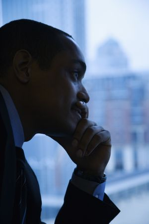 out think: Perfil de Close-up de un empresario estadounidense de mid-adult con la mano en la barbilla en frente de la ventana. Formato vertical. Foto de archivo