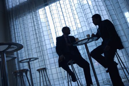 Tilt view silhouette of African-American and Asian businessmen sitting at a table having coffee in front of a curtained window. photo