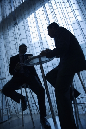 cropped out: Tilt view silhouette of African-American and Asian businessmen sitting at a table and having coffee in front of a curtained window. Vertical format.