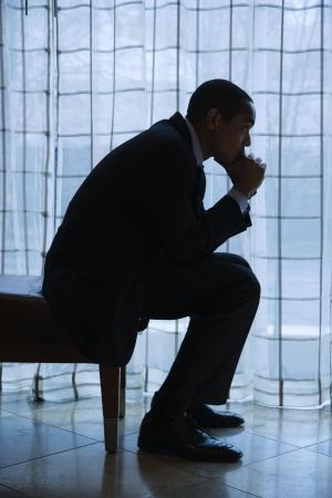 Profil des African-American mid-adult Geschäftsmann sitzen und mit der Hand auf Kinn neben einem curtained Fenster denken. Vertikale Format.