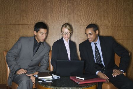 Three diverse businesspeople sit at a small table and look at a laptop together. Horizontal format. photo