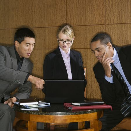 Three diverse businesspeople sit at a small table and look at a laptop together. Square format. Stock Photo - 6455384
