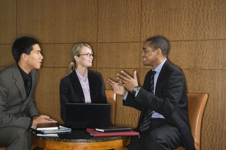 Three diverse businesspeople sit at a small table with a laptop and talk together. Horizontal format.
