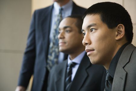 Asian businessman in the foreground with African-American businessman and a third businessman in the background. Horizontal format. Stock Photo