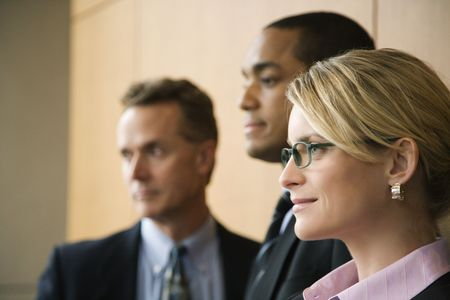 Close-up of Caucasian mid-adult businesswoman with two businessmen in background. Horizontal format.