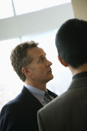 Cropped view of a Caucasian middle-aged businessman and a young adult businessman in a discussion. Vertical format. photo