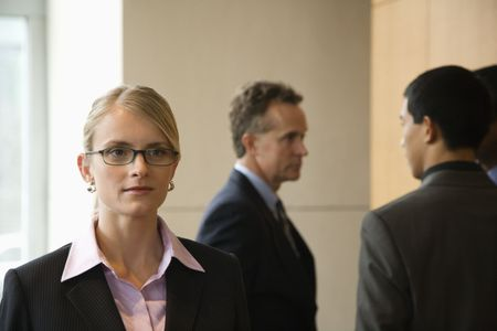 Caucasian mid-adult business woman in foreground with group of businessmen in the background. Horizontal format. photo