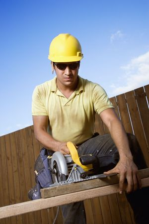 Male Caucasian construction worker in safety glasses and a hardhat cutting wood with a circular saw. Vertical shot. Stock Photo - 6455282