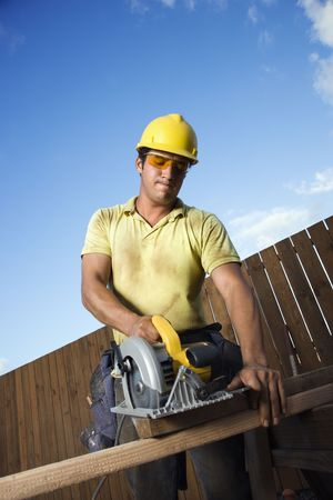 woodworking: Male Caucasian construction worker in safety glasses and a hardhat. He is cutting wood with a circular saw. Vertical shot.