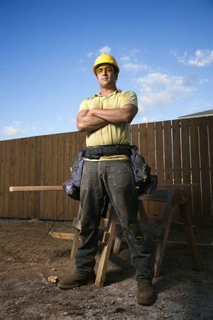 workbench: Male Caucasian construction worker stands confidently and looks into the camera. His arms are folded across his chest and a workbench can be seen behind him. Vertical shot.