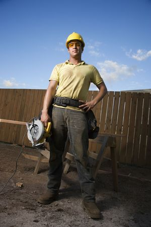 power saw: Worker in a hardhat and safety glasses stands at a construction site with a hand on his hip. He holds a circular saw with the other hand. Vertical shot. Stock Photo