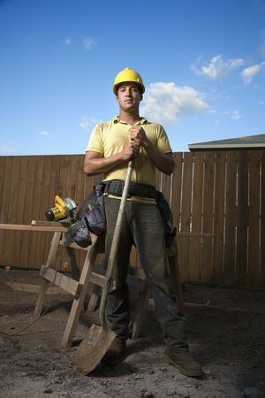 Male Caucasian construction worker in a yellow hardhat is holding a shovel while looking at the camera. Vertical shot. photo