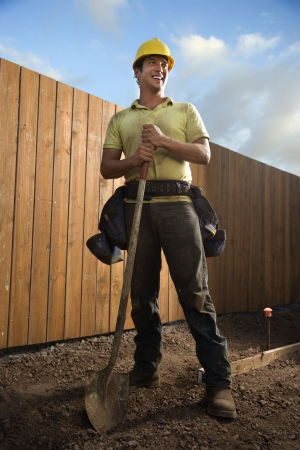 Construction worker leans on a spade and smiles to the side at a construction site. Vertical shot. Stock Photo - 6455252