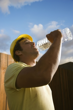 sediento: Vista lateral de un trabajador de construcci�n del C�ucaso masculino como bebidas de �l de una botella de agua de pl�stico. Pueden verse una valla y el cielo azul en el fondo. Un disparo vertical.