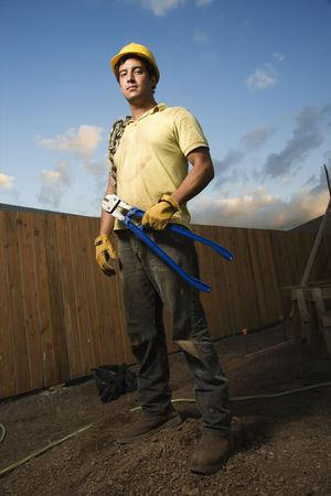 dirty man: Construction worker stands on a mound of dirt while holding bolt cutters. He has a chain wrapped around his shoulder and a hardhat on. Vertical shot.