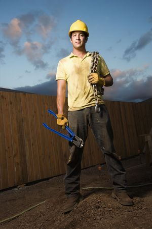 sweaty: Attractive male construction worker in a hardhat stands at a construction site with bolt cutters and a chain. Vertical shot. Stock Photo