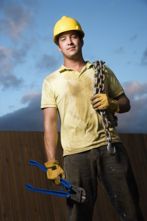short gloves: Attractive male construction worker in a yellow hardhat smiles into the camera. He holds a heavy chain on his shoulder and bolt cutters in his hand. Vertical shot. Stock Photo