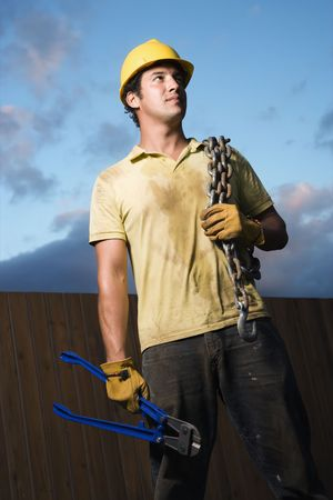 Male Caucasian construction worker wearing a yellow hardhat stands with heavy chain on his shoulder and bolt cutters in his hand. Vertical shot. photo
