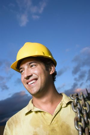Attractive Caucasian construction worker in a yellow hardhat carries a heavy chain over his shoulder while smiling to the side. Vertical shot. photo