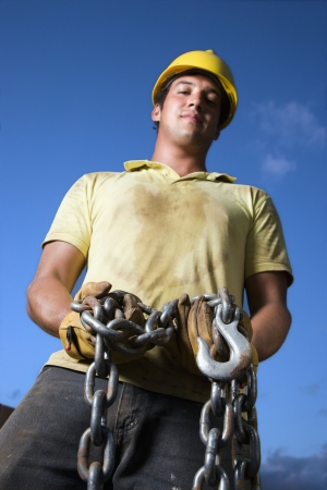 Attractive male construction worker wearing a yellow hardhat and work gloves looks down at the camera while holding a heavy chain and hook. Vertical shot
