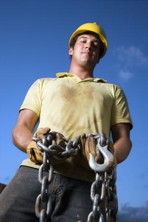Attraktive männlichen Bauarbeiter, die eine gelbe Hardhat und Arbeit Handschuhe tragen sucht nach unten auf der Kamera halten eine schwere Kette und Hook. Vertikale shot
