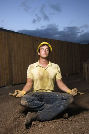 construction workers: Caucasian male construction worker sits in a yoga meditation pose while wearing a yellow hardhat. Vertical shot.