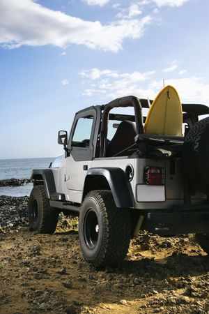 SUV parked on a rocky beach with a surfboard sticking out of the back seat. Vertical format. Stock Photo