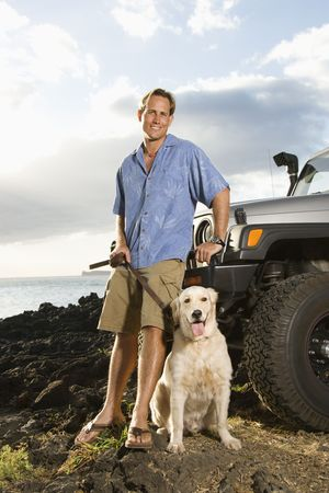 mans best friend: A smiling man leans against his SUV at the beach as he holds his dogs leash and looks at the camera. Vertical format. Stock Photo