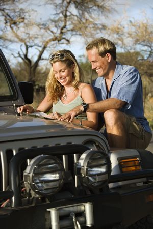 A smiling man and woman look at a map spread out on the hood of a car. Vertical format. photo