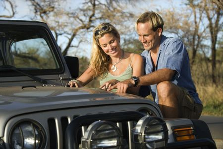 A smiling man and woman look at a map spread out on the hood of a car. Horizontal format. photo