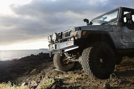 Low angle view of front of SUV on a rocky beach. Horizontal format. photo