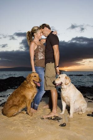 A man and woman hold the leashes of their dogs as they hug at a beach. Vertical format. photo