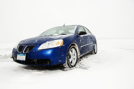 caked: Blue sedan caked in ice and snow sits parked amongst a winter backdrop. Horizontal shot.