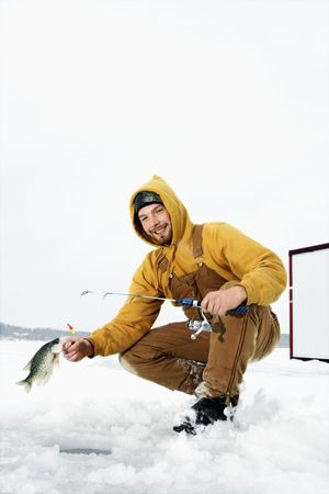 Young man pulls a fish out of a hole in the ice. He is holding a fishing rod and wearing snow gear. Vertical shot. photo