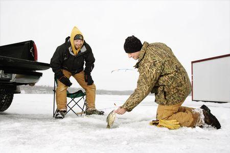 fishing gear: Two young men ice fishing in a winter environment. Horizontal shot. Stock Photo
