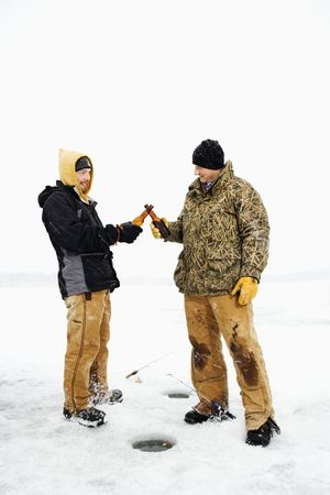 Two young men clink beers bottles while ice fishing. Vertical shot. photo