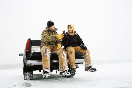 Two young men enjoy a beer while sitting on the tailgate of a truck in a winter environment. Horizontal shot. Stock Photo - 6455211