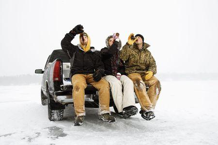 hombre tomando cerveza: Dos hombres j�venes y una mujer joven que beber cerveza mientras estaba sentado en el port�n trasero de un cami�n en un entorno de invierno. Horizontal de disparo. Foto de archivo