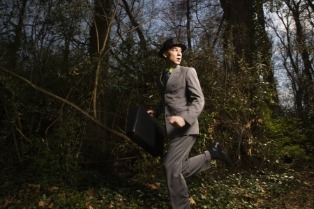 Young businessman runs through the woods, looking behind him while holding a briefcase. Horizontal shot. Stock Photo