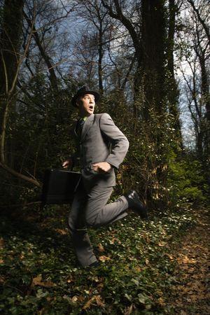 Junge Geschäftsmann führt fearfully durch die Wälder, während hinter. Vertikale erschossen.