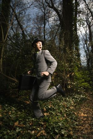 Young businessman fearfully runs through the woods while looking behind. Vertical shot.