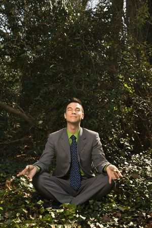 Young businessman sits in a lotus position meditating in the woods with closed eyes and a smile. Vertical shot. Stock Photo - 6455432