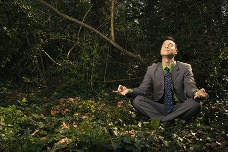 Young businessman sits in a lotus position meditating in the woods with closed eyes and a smile. Horizontal shot.