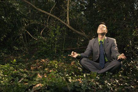 Junge Geschäftsmann befindet sich in einer Lotus-Position im Wald mit geschlossenen Augen und einem Lächeln meditieren. Horizontal gedreht. Lizenzfreie Bilder