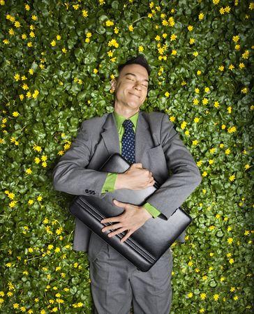 Junge Geschäftsmann mit Aktenkoffer entspannenden in eine Blume-Patch mit Zufriedenheit lächelnd.