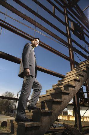 Junge Geschäftsmann Spaziergänge bis eine hölzerne Treppe in einem verlassene Gebäude. Vertikale erschossen. Lizenzfreie Bilder