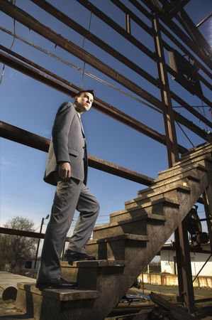 Young businessman walks up a wooden staircase in an abandoned building. Vertical shot. Stock Photo