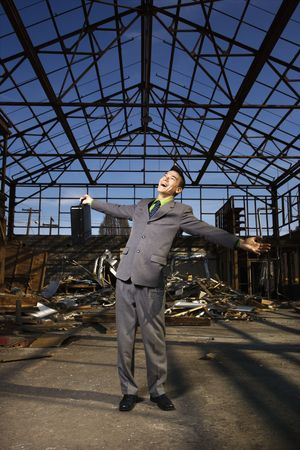 Young businessman smiles with open arms as he stands holding his briefcase in an abandoned building. Vertical shot Stock Photo - 6455311