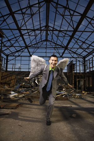 Young businessman smiles with angel wings on his back and attempts takeoff in an abandoned building. Vertical shot. photo