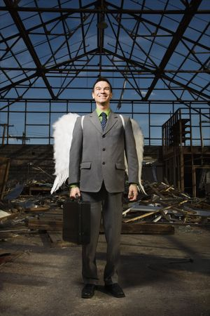 Young businessman with angel wings smiles at the camera while standing in an abandoned building. Vertical shot. photo